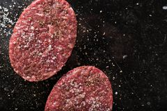 Meat for burgers, grilling, barbecue, bbq. Fresh, spicy, uncooked, delicious beef for hamburgers on dark background with. Copy space closeup Royalty Free Stock Image