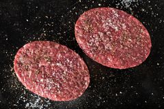 Meat for burgers, grilling, barbecue, bbq. Fresh, spicy, uncooked, delicious beef for hamburgers on dark background with. Copy space closeup Royalty Free Stock Photo