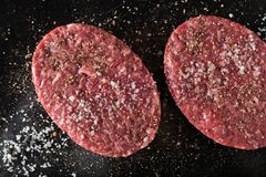 Meat for burgers, grilling, barbecue, bbq. Fresh, spicy, uncooked, delicious beef for hamburgers on dark background with. Copy space closeup Stock Photo