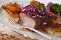 Meat with caramelized onions on a plate closeup. horizontal Stock Photography