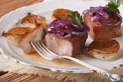 Meat with caramelized onions and sauce on a plate closeup Royalty Free Stock Photo