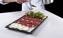 Meat carpaccio seasoned with olive oil by chief royalty free stock images