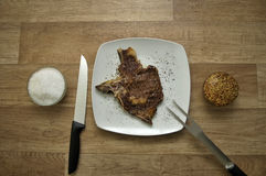 Meat with carving fork and chef knife. Gourmet meat meal with rice and Dijon mustard served on a wooden table. Top view. One of a three images series royalty free stock photo