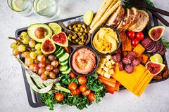 Meat and cheese appetizer platter. Sausage, cheese, hummus, vegetables, fruits and bread on black tray