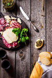 Meat and cheese on dark chopping board. Royalty Free Stock Photography