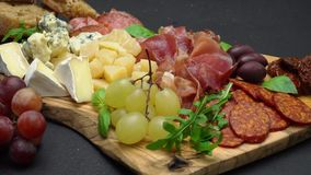 Meat and cheese plate antipasti snack with Prosciutto, melon, grapes and cheese stock footage