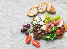 Meat and cheese plate on rustic wood board over a white paper ba Stock Image