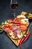 Meat and cheese plate and wine with sausage, prosciutto, olives. On concrete background stock image