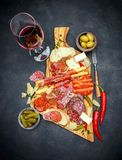 Meat and cheese plate and wine with sausage, prosciutto, olives. On concrete background royalty free stock photo