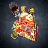 Meat and cheese plate and wine with sausage, prosciutto, olives. On concrete background royalty free stock photography