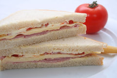 Meat and cheese sandwich. A closeup view of two halves of a meat and cheese sandwich on white bread with a whole red tomato in the background royalty free stock image