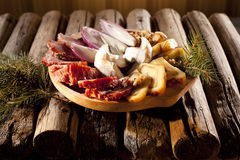 Meat and cheese on table. Traditional food and vegetables on rustic table Royalty Free Stock Photos