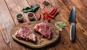 Meat with chili, cayenne powder and some spices. Uncooked meat with chili, cayenne powder and some spices on wooden surface royalty free stock photography