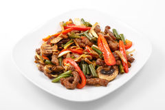 Meat in Chinese, pork, Chinese sauce, mushrooms, green beans, bell pepper. In a white plate on a white background stock photo