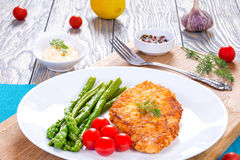 Meat chop, asparagus and cherry tomatoes, served Royalty Free Stock Photo