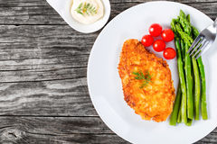 Meat chop fried in tempura with asparagus and cherry tomatoes Royalty Free Stock Photography