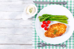 Meat chop fried in tempura with asparagus and cherry tomatoes Stock Images