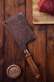 Meat cleaver butcher knife. With raw beef meat fillet on wooden table and 1lb iron weight stock photography