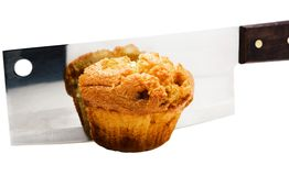 Meat cleaver cutting a cupcake. Isolated over white stock images