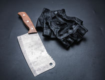 Meat cleaver and fingerless leather gloves Stock Photo