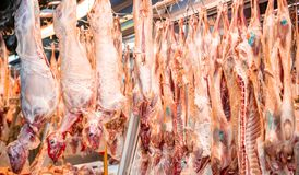 Meat concept. Lamb, sheep hanged on hooks, butcher shop. Uncooked mutton for background, closeup. Meat market concept. Lamb, sheep hanged on hooks out of butcher stock photo