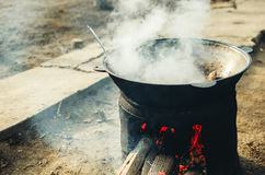 The meat is cooked in a cauldron on the street. The cauldron on the fire street food cooking pilaf, meat picnics holidays Royalty Free Stock Image