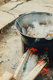 The meat is cooked in a cauldron on the street. The cauldron on the fire street food cooking pilaf, meat picnics holidays Royalty Free Stock Photography
