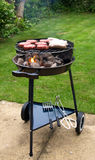 Meat cooking on charcoal grill. Meat cooking on a backyard charcoal barbecue grill Royalty Free Stock Photography