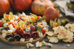 Meat cut, ham, cheese, physalis next to figured cookies and pumpkins at a picnic Royalty Free Stock Photo