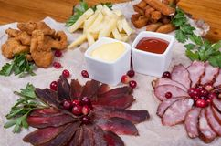 Food on the table. Meat cut with potato, vegetables, sauces and croutons Stock Photography