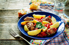 Meat cutlets baked with potatoes, tomatoes and red pepper Royalty Free Stock Image