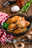 Meat cutlets in frying pan on wooden rustic table Stock Photography