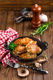 Meat cutlets in frying pan on wooden rustic table Royalty Free Stock Images
