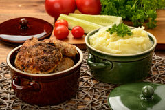 Meat cutlets and mashed potatoes in ceramic pots. Stock Images
