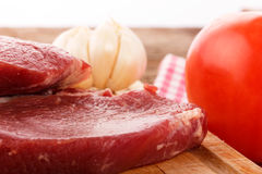 Meat on a cutting board with tomato and garlic Stock Photo