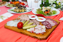 Meat cutting on wooden plate on banquet table Stock Image
