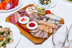 Meat cutting on wooden plate on banquet table Stock Photography