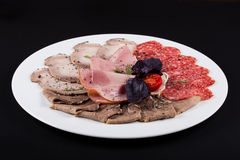 Meat delicatessen plate arranged with cherry tomato, pepper and bazil. ham assortment on black background.  Royalty Free Stock Photo