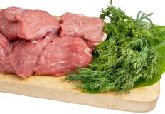 Meat and dill. On wooden plate isolated on a white background Royalty Free Stock Photo