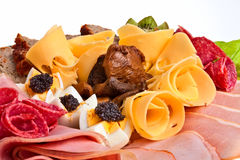 Meat dish. Dish with sliced ham, cheese and salami rolls, boiled eggs with black caviar and more Royalty Free Stock Image
