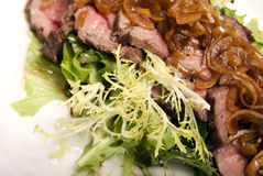 Meat dish. Meat served with salad and onion royalty free stock photo