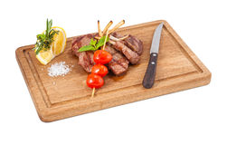 Meat dish. On a chopping wooden board, tomatoes and seasonings stock photography