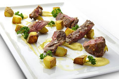 Meat Dish Cut Grilled Steak with Potatoes and Parsley. On square white plate Stock Photography