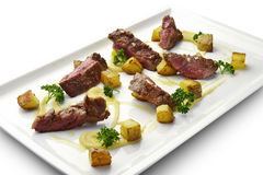 Meat Dish Cut Grilled Steak with Potatoes and Parsley. On square white plate Royalty Free Stock Images