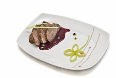 Meat dish decorated with leek. Royalty Free Stock Image