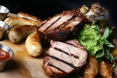Meat dish with steaks, pork knuckle, homemade sausage and baked potatoes. royalty free stock image