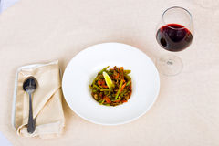 Meat dish with vegetables in a plate and a glass of red wine Stock Image
