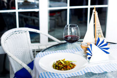 Meat dish with vegetables in a plate and a glass of red wine Royalty Free Stock Photography