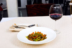 Meat dish with vegetables in a plate and a glass of red wine Stock Photo