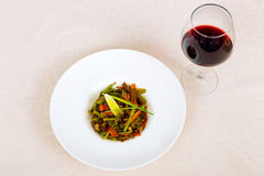Meat dish with vegetables in a plate and a glass of red wine Stock Photography
